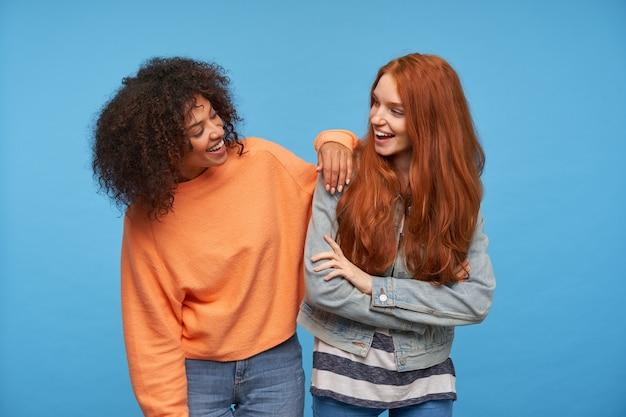 Tiro al coperto di affascinanti amiche positive che ridono allegramente mentre si guardano l'un l'altro, di buon umore stando in piedi sul muro blu Foto Gratuite