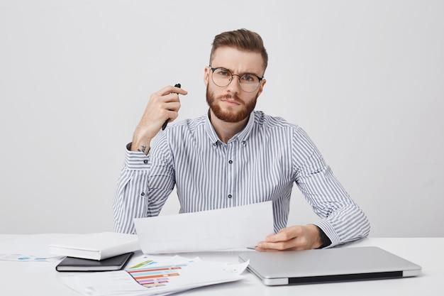 Tiro al coperto di capo o datore di lavoro maschio giovane rigoroso fiducioso, ha barba e acconciatura alla moda Foto Gratuite