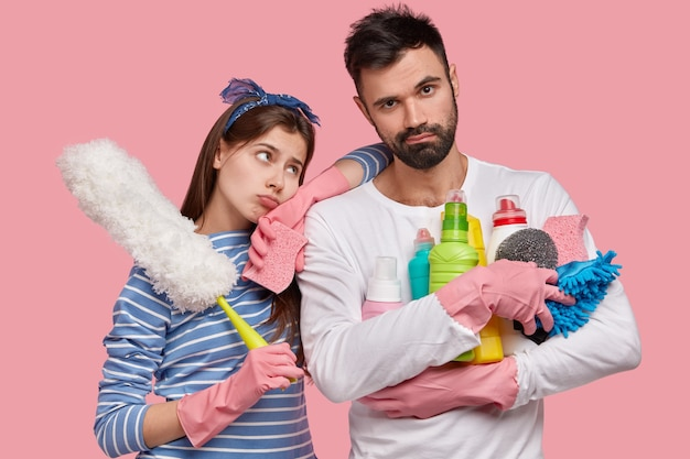 Indoor shot of displeased lady and male use rag, chemical detergents and brush for cleaning room, have dejected miserable exxpressions Free Photo