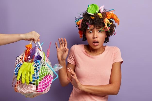 Tiro al coperto di donna afroamericana insoddisfatta fa il gesto protettivo contro il sacchetto netto con immondizia di plastica Foto Gratuite