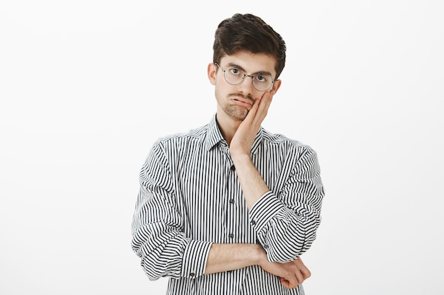 Tiro al coperto di modello maschio maturo annoiato stufo in camicia a righe, con il palmo sulla guancia ed espirando, fissando con indifferenza e noia, infastidito dalla lunga riunione in ufficio Foto Gratuite