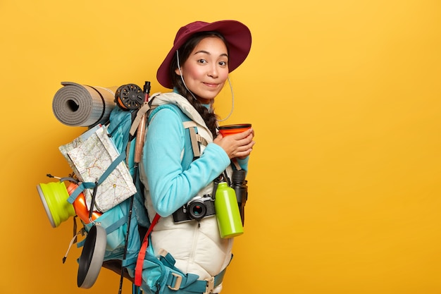 Riprese in interni di una viaggiatrice fa una pausa caffè, ama il viaggio, trasporta lo zaino con le cose necessarie e la mappa, ha un lungo percorso, indossa un cappello e abiti comodi Foto Gratuite