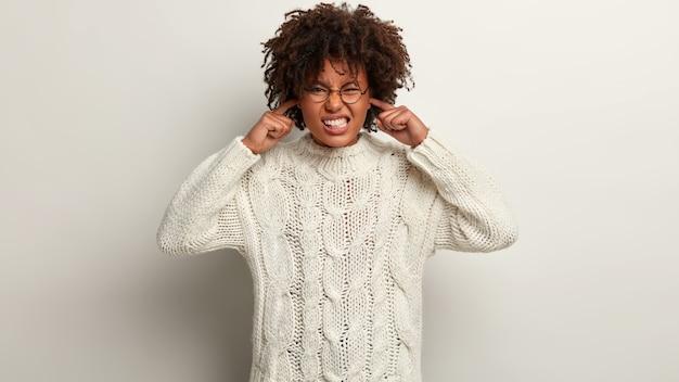 Tiro al coperto di donna frustrata con pelle scura, capelli ricci, tappi le orecchie, stringe i denti, evita suoni o rumori sgradevoli, ha un'espressione insoddisfatta, indossa un maglione bianco lavorato a maglia, isolato su un muro bianco Foto Gratuite