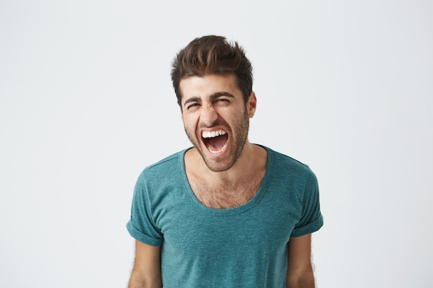 Indoor shot of furious young good-looking european man in casual cloth screaming with anger and rage, keeping his eyes closed. student having an argument with his girlfriend. human face expressions, Free Photo