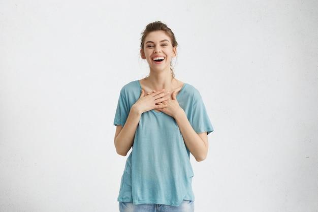 Tiro al coperto di felice bella donna con i capelli chignon sorridente allegramente, tenendo le mani sul seno, soddisfatto Foto Gratuite