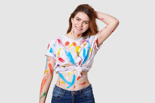 Indoor shot of happy european female painter has dirty body and white t shirt with colourful paints, shows belly, keeps hand behind head, isolated over white wall creats artwork or masterpiece Free Photo