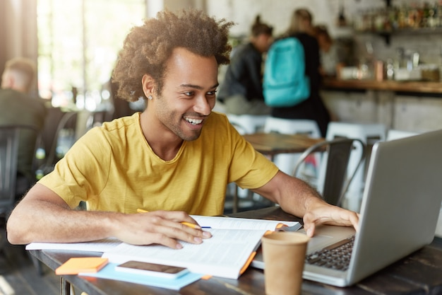 Indoor shot of happy student male with curly hair dressed casually sitting in cafeteria working with modern technologies while studying looking with smile in notebook receiving message from friend Free Photo