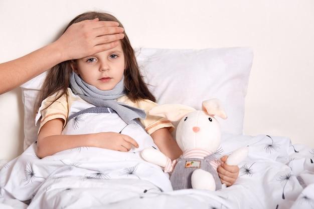 Tiro al coperto di bambina con i capelli biondi sdraiato nel suo letto, abbracciando il giocattolo preferito, avendo la mano sconosciuta sulla fronte, controllando la temperatura Foto Gratuite
