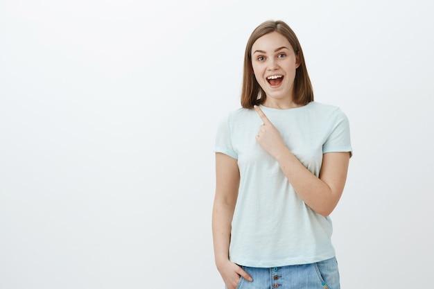 Снимок изумленной энергичной и оптимистичной симпатичной женщины в модной футболке, радостно улыбающейся, указывающей в левый верхний угол с указательным пальцем у груди, наслаждающейся проведением времени весело и весело Бесплатные Фотографии