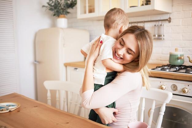 Снимок в помещении привлекательной блондинки молодой матери, приятно проводящей время дома, обнимающей малыша, сидящего за обеденным столом в уютной кухне, улыбаясь и наслаждаясь счастливыми сладкими моментами своего материнства Бесплатные Фотографии