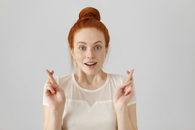 Снимок привлекательной рыжей девушки с пучком волос в помещении, возбужденный, суеверный и наивный вид Бесплатные Фотографии