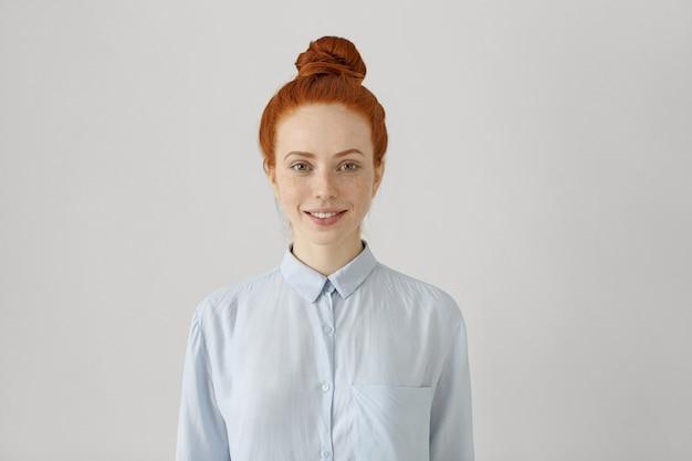 幸せそうに笑ってシャツでお団子と魅力的な若い赤毛の女性の屋内撮影 無料写真