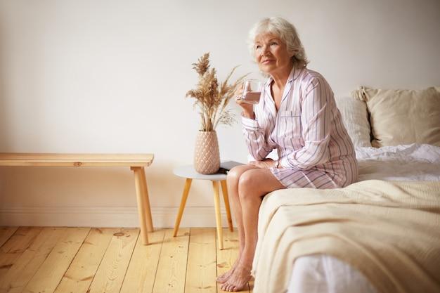 Крытый снимок босой привлекательной седой женщины-пенсионерки, сидящей на кровати с ногами на деревянном полу, держащей стакан и пьющей пресную воду по утрам. люди, образ жизни, время сна и концепция старения Бесплатные Фотографии