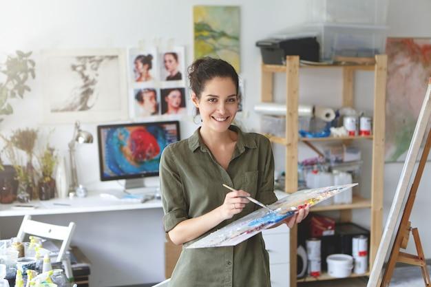 美しいブルネットの女性画家のシャツを着て、イーゼルの近くに立って手でペイントブラシを押しながら傑作を作成し、ペイントして嬉しそうに笑っている室内のショット 無料写真