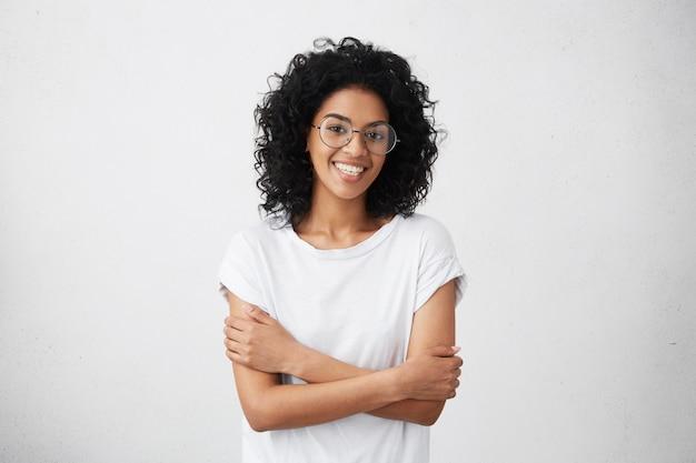 Крытый снимок красивой счастливой афро-американской женщины, весело улыбаясь, держа руки сложенными, отдыхая в помещении после утренних лекций в университете Бесплатные Фотографии
