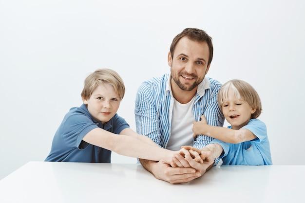 Снимок в помещении: красивые счастливые папа и сыновья сидят за столом и широко улыбаются, держатся за руки и смотрят с широкой улыбкой, дурачатся Бесплатные Фотографии