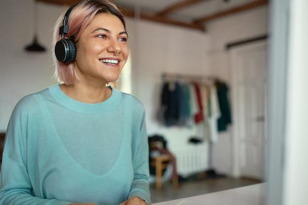집에 앉아 온라인 시험을하는 데 무선 헤드폰을 사용하는 파란색 셔츠에 아름 다운 행복 학생 여자의 실내 샷. 사람, 교육, 학습, 기술 및 전자 기기 무료 사진