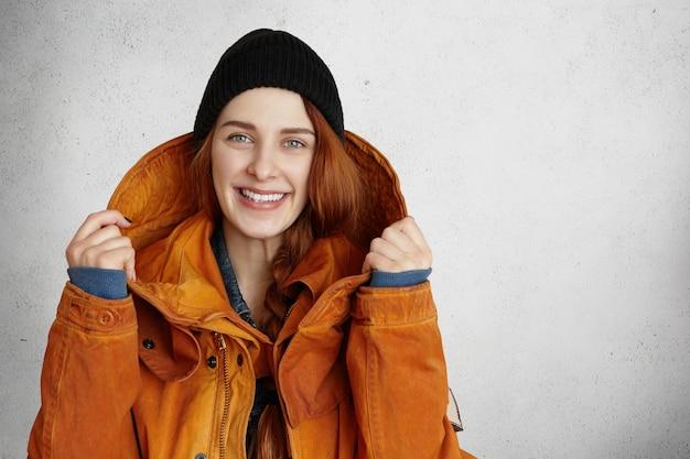 幸せそうに笑って、黒い帽子の美しい赤毛の白人少女の屋内撮影 無料写真
