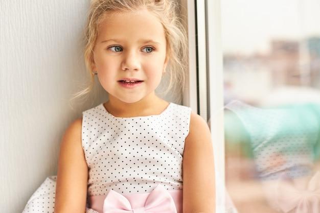창턱에 앉아 점선 드레스에 아름 다운 슬픈 백인 여자의 실내 샷, 화가 모습, 외로움, 직장에서 부모를 기다리고 있습니다. 사람, 어린이, 라이프 스타일 및 외로움 개념 무료 사진