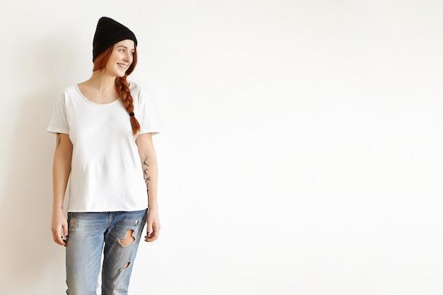 白いスタジオの壁に対して隔離されるポーズスタイリッシュな服で美しい若い女性の屋内撮影 無料写真
