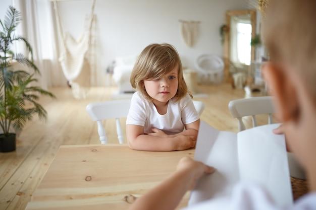 家の木製のテーブルに座って、紙を持っている認識できない若い父親と一緒に宿題をチェックしている魅力的なかわいい女の子の屋内ショット。子供の顔に選択的な焦点 無料写真