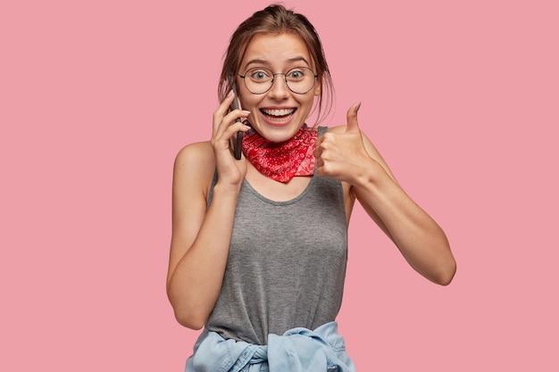 陽気な白人女性の屋内ショットは、大丈夫なジェスチャーを示し、親指を上げ続け、彼女の承認を表明し、携帯電話で話します 無料写真