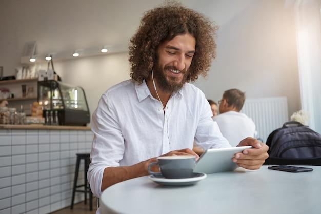 カフェのインテリアにポーズをとって、音楽を聴き、コーヒーを飲みながら友達とおしゃべりしながら、ひげと巻き毛の茶色の髪を持つ陽気な若い男の屋内ショット 無料写真