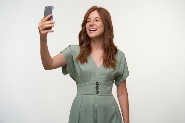 쾌활한 젊은 빨간 머리 여성 포즈의 실내 샷, 그녀의 전화로 자신의 사진을 만들고, 행복하게 미소 무료 사진