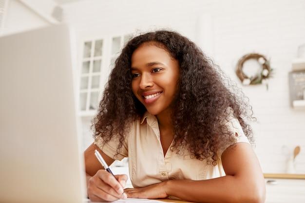 ポータブルコンピューターを使用してリモートで作業し、ダイニングテーブルに座っている自信を持って陽気な若い暗い肌の女性フリーランサーの屋内ショット。現代の電子ガジェット、仕事と職業の概念 無料写真