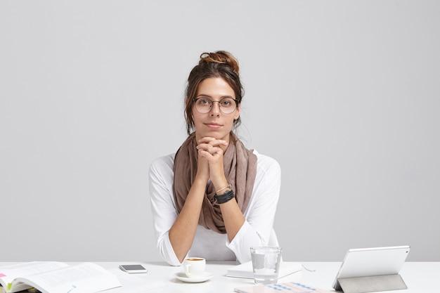 自信を持って女性起業家の屋内撮影は、オフィスの机に座って、新しいプロジェクトの開発に取り組んでおり、コーヒーブレイクがあります。 無料写真