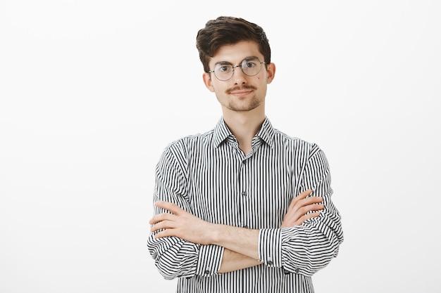 Снимок в помещении: раздраженный напряженный европейский мужчина с бородой и усами в модных очках, держащий руки на груди и ожидающий, обиженный и желающий услышать извинения Бесплатные Фотографии