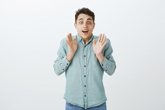 Крытый снимок взволнованной счастливой мужской модели в повседневной рубашке Бесплатные Фотографии