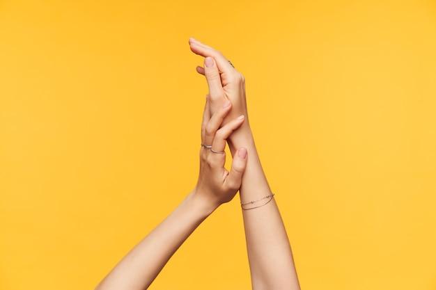 노란색 배경 위에 절연 그것에 Creame을 적용하는 동안 부드럽게 만지고 젊은 아가씨의 공정한 피부 손의 실내 샷. 몸과 손 관리 개념 무료 사진