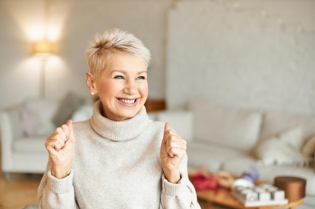 ポジティブなニュースを楽しんだり、恍惚とした表情をしたり、笑ったり、拳を握りしめたりする、タートルネックのセーターを着たファッショナブルな大喜びの成熟した女性の屋内ショット。成功と成果の概念 無料写真