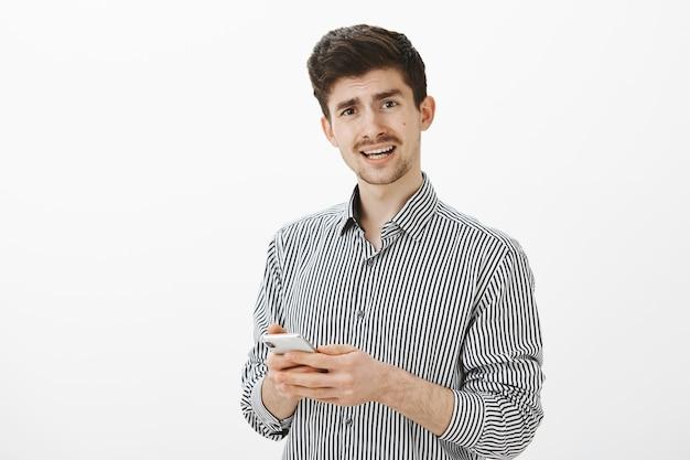 Снимок в помещении: разочарованный и недовольный зрелый парень с усами в повседневной полосатой рубашке, вопросительно смотрит, задает вопрос, держит смартфон и получает запутанное сообщение Бесплатные Фотографии