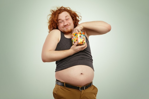 Снимок смешного рыжего молодого мужчины в помещении, сжимающего пригоршню конфет из стеклянной банки Бесплатные Фотографии