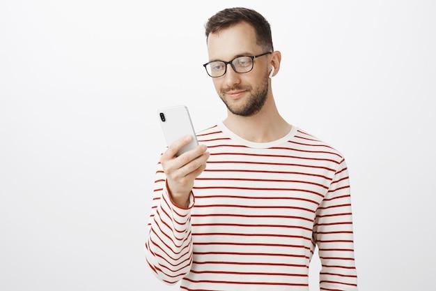Снимок красивого расслабленного европейца в очках, держащего смартфон, выбирающего песню для прослушивания и в беспроводных наушниках внутри помещения Бесплатные Фотографии