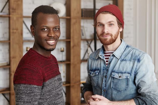 Красивый африканский мужчина в уютном свитере, стоящий рядом со своим бородатым другом-хипстером, в помещении Бесплатные Фотографии