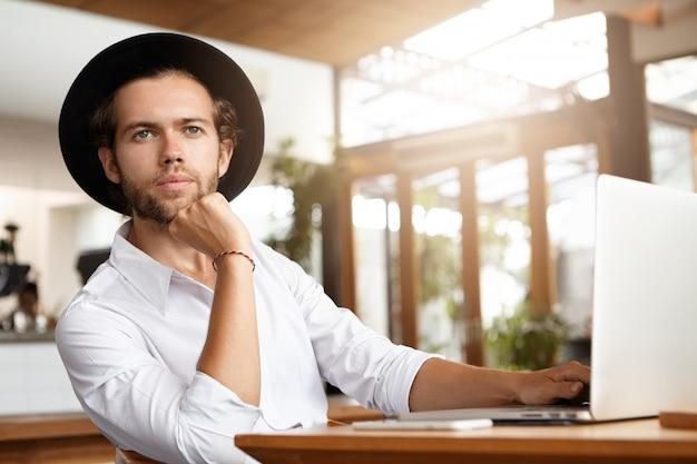 ジェネリックラップトップpcでwi-fiを使用して彼のブログの新しい投稿に取り組んでいる帽子のハンサムな若いブロガーの屋内ショット 無料写真