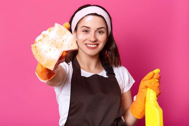Внутренний снимок счастливой кавказской молодой женщины в белой повседневной футболке, ободке для волос, коричневом фартуке, держит губку и моющее средство, готов сделать домашнюю работу, стоит улыбается на розовой стене. концепция гигиены Бесплатные Фотографии