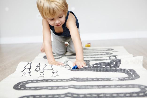 Крытый снимок счастливого жизнерадостного кавказского двухлетнего мальчика со светлыми волосами, играющего со своими игрушками, ползущего по ковру в детской комнате и выглядящего заинтересованным. Бесплатные Фотографии