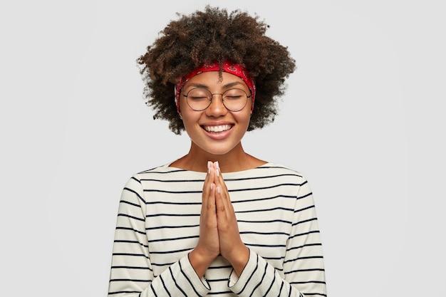 Снимок в помещении: счастливая, довольная улыбающаяся женщина, мечтающая о многом, позирует в молитвенном жесте и загадывает Бесплатные Фотографии