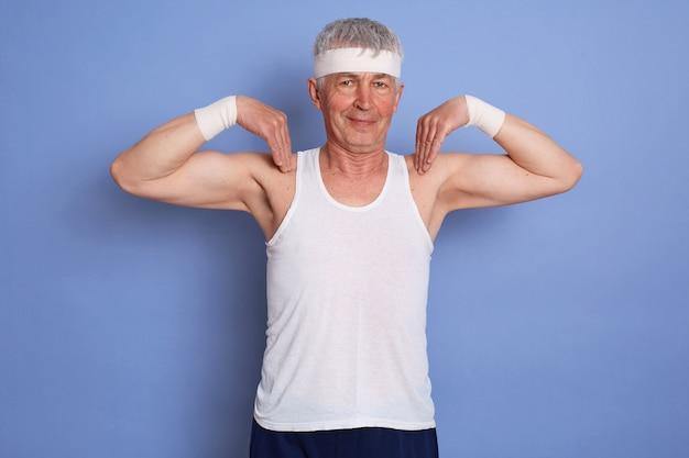 青い壁に対して体力トレーニングを楽しんで、体操をして、彼の肩に指を持って幸せなエネルギッシュな年配の男性の屋内ショット 無料写真