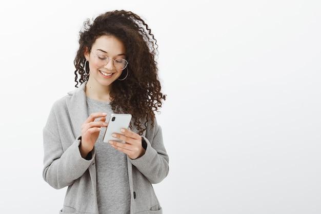 Крытый снимок счастливой модной женщины с модными серьгами и очками, стоящей в сером пальто Бесплатные Фотографии