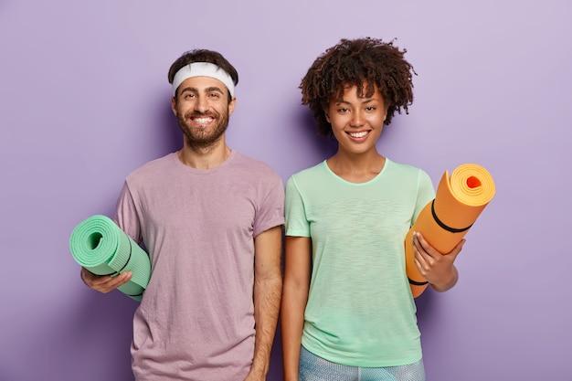 피트니스 훈련 준비가 된 행복한 혼혈 여성과 남성의 실내 샷, 팔 아래에 말아 올린 매트를 들고, 즐거운 얼굴을하고, 활동적인 삶과 일상적인 운동을 즐기고, 캐주얼 한 스포츠 복장을 착용하십시오. 무료 사진