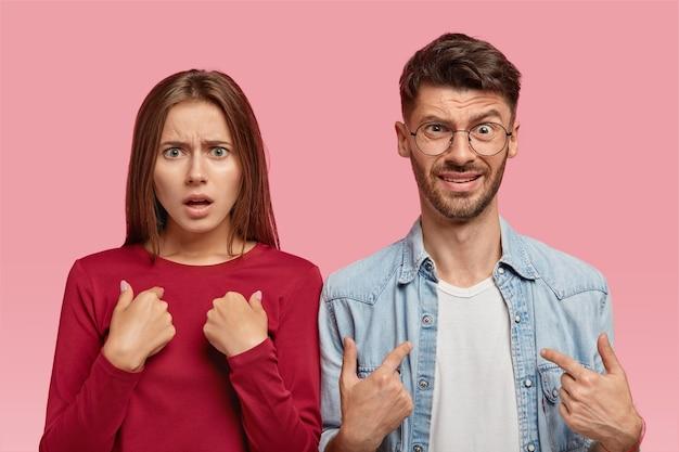 Возмущенные кавказские молодая женщина и мужчина указывают на себя в помещении Бесплатные Фотографии