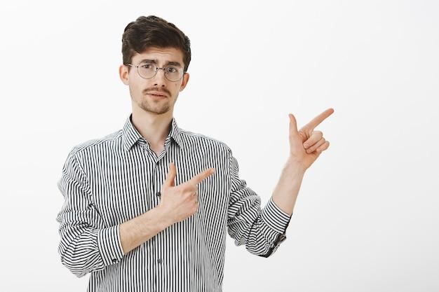 Снимок в помещении небезопасного взрослого кавказского бородатого парня с усами в модных круглых очках, который показывает вправо жестом пистолета, с любопытством приподнимает бровь, неуверенно показывает направление Бесплатные Фотографии