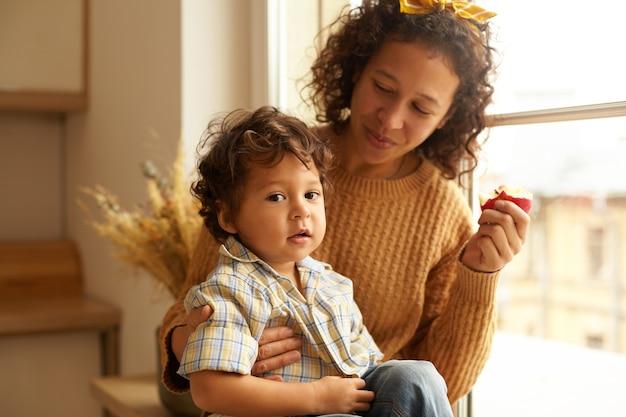 彼女の膝の上に愛らしいぽっちゃりした男の子と窓辺でリンゴを食べるセーターとスカーフを身に着けている楽しい若い女性の屋内ショット。家族の絆、人間関係、愛と親の概念 無料写真
