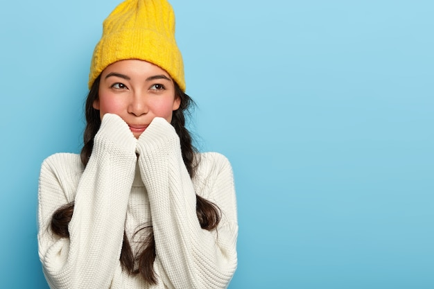사랑스러운 갈색 머리 여자의 실내 촬영은 노란색 모자와 흰색 스웨터를 입고 꿈꾸는 표정을 가지고 멀리 보이는 파란색 벽에 서 무료 사진