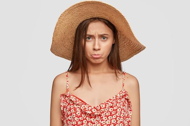夏の帽子と赤いドレスで気分を害した悲しい女性の屋内ショット 無料写真